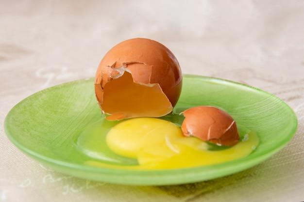Seitenansicht eines rohen rohen gebrochenen eies in einer grünen platte auf dem küchentisch. gelbes eigelb und flüssiges eiweiß. zutat zum backen, omelett