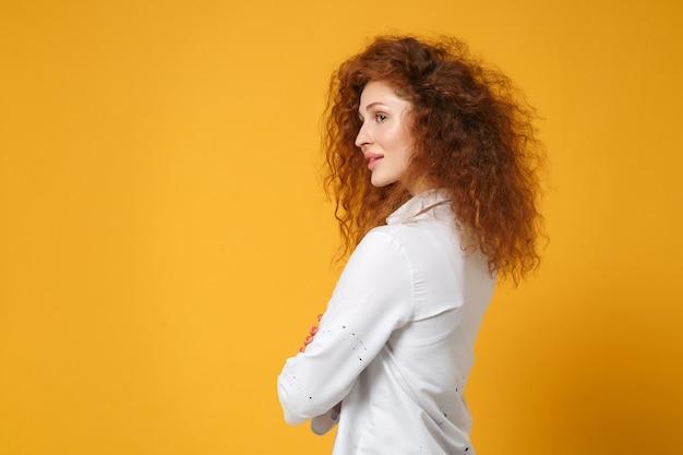 Seitenansicht eines schönen jungen rothaarigen mädchens in lässigem weißem hemd, das isoliert auf gelb-orangefarbener wand posiert