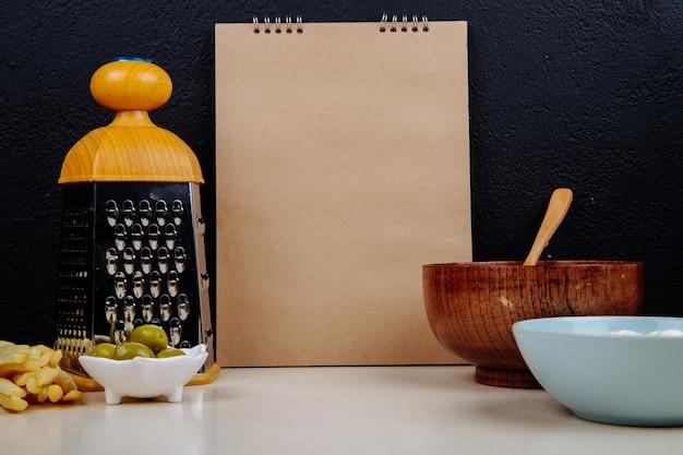 Seitenansicht eines skizzenbuchs, hüttenkäse in einer holzschale mit einem löffel und einer reibe, eingelegte oliven am schwarzen wandtisch