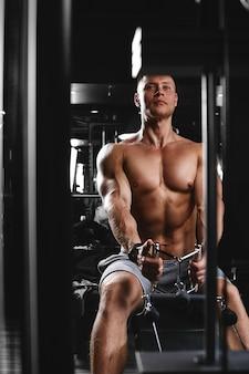 Seitenansicht eines starken jungen mannes mit athletischem körper, der in einem dunklen fitnessstudio übungen an fitnessgeräten macht. kopieren sie platz, werbebanner, fitnessmotivation, gesunder körper, gesunder geist.