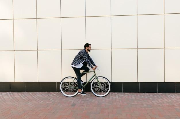 Seitenansicht eines stilvollen bärtigen mannes, der fahrrad auf die stadtstraße fährt.