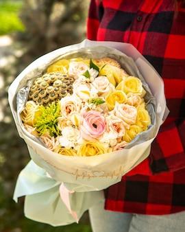 Seitenansicht eines straußes von rosa farbrosen mit rosa ranunkeln und chrysanthemen-santini-blüten