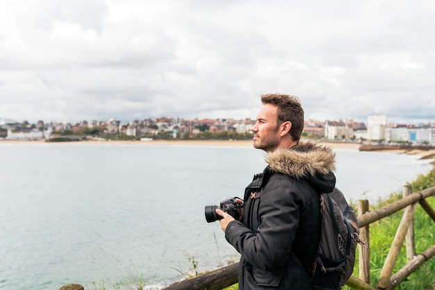 Seitenansicht eines stylischen erwachsenen reisenden in freizeitkleidung und stirnband, der das plätschernde meer fotografiert