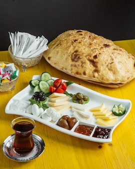 Seitenansicht eines tellers mit frühstücksnahrung mit frischem gemüse, oliven, käse, honig und marmelade, serviert mit tee