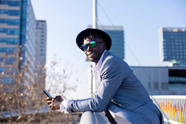 Seitenansicht eines tragenden hutes und der sonnenbrille des jungen mannes des schwarzafrikaners, die auf einem metallischen zaun bei einem handy draußen verwenden sich lehnen
