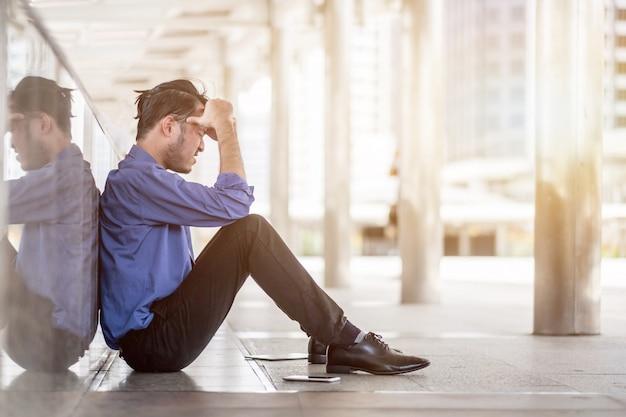 Seitenansicht eines traurigen mannes mit einer hand auf dem kopf, der im traurigen geschäftsverliererkonzept des büros sitzt