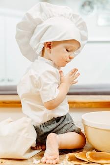 Seitenansicht eines ungezogenen kleinen jungen im weißen kochanzug, der barfuß auf dem küchentisch sitzt