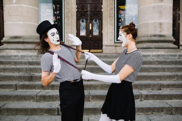 Seitenansicht eines verärgerten weiblichen pantomimen, der männlichen pantomimehalter vor treppenhaus zieht