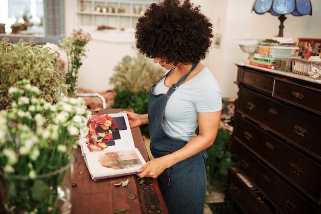 Seitenansicht eines weiblichen floristen, der blumenfotoalbum betrachtet