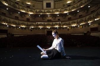 Seitenansicht eines weiblichen Pantomimen, der auf Stadiumslesemanuskript sitzt