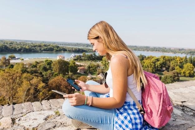 Seitenansicht eines weiblichen wanderers, der mobiltelefon an draußen verwendet