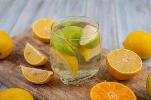Seitenansicht entgiftungswasser in einem glas mit limettenschnitzen und einer halben orange und zitrone auf einem schneidebrett