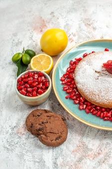 Seitenansicht erdbeerkuchen blauer kuchenteller mit erdbeeren und granatapfel neben der zitronenschale mit granatapfel und keksen auf dem teller