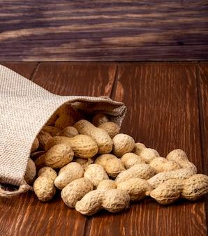 Seitenansicht erdnüsse in der schale von einer tasche auf einem holztisch