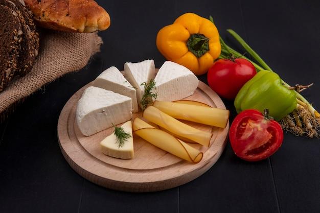 Seitenansicht feta-käse und tomaten paprika und frühlingszwiebeln auf einem stand auf einem schwarzen hintergrund