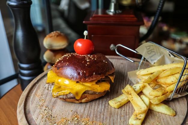 Seitenansicht fleischburger mit tomaten und pommes mit gewürzen auf einem ständer