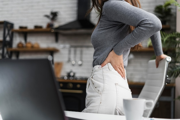 Seitenansicht frau, die rückenschmerzen während der arbeit von zu hause aus hat