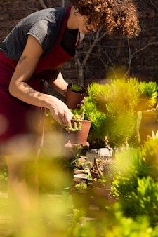 Seitenansicht frau, die sich um ihre pflanzen kümmert