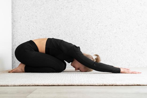Seitenansicht frau, die yoga praktiziert