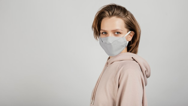 Seitenansicht frau im kapuzenpulli mit maske