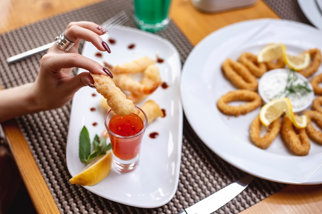 Seitenansicht frau isst garnelen im teig mit süßer chilisauce und einer zitronenscheibe