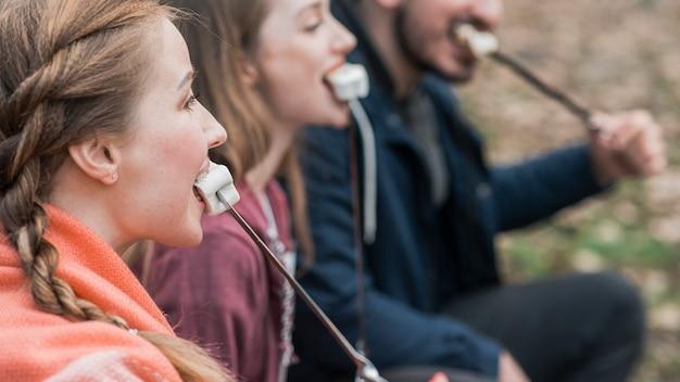 Seitenansicht freunde essen marshmallow