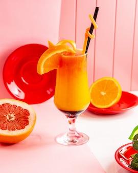 Seitenansicht frisch gepresste grapefruit mit orangensaft mit grapefruitscheiben und orange