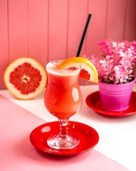 Seitenansicht frisch gepresster grapefruitsaft mit grapefruitscheiben