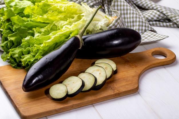 Seitenansicht frische auberginen mit scheiben auf einem brett mit salat