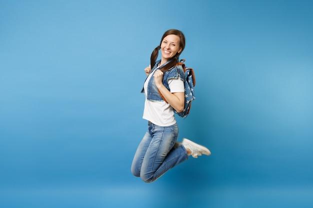 Seitenansicht ganzaufnahme der jungen fröhlichen glücklichen studentin in denimkleidung mit rucksackspringen einzeln auf blauem hintergrund. ausbildung an der fachhochschule. kopieren sie platz für werbung.