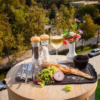 Seitenansicht gebratener fisch mit salat, tomaten, zwiebeln und soße auf einem schwarzen teller, ein glas weißwein auf einem kleinen runden tisch mit blick auf die stadt