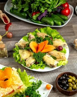 Seitenansicht gekochtes huhn mit kräutern auf salatblatt mit karottenscheiben