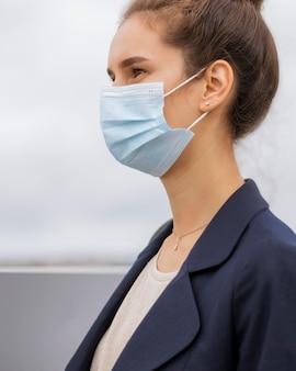 Seitenansicht geschäftsfrau, die eine medizinische maske trägt