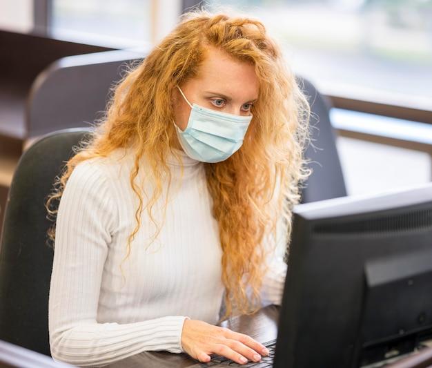 Seitenansicht geschäftsfrau, die medizinische maske trägt
