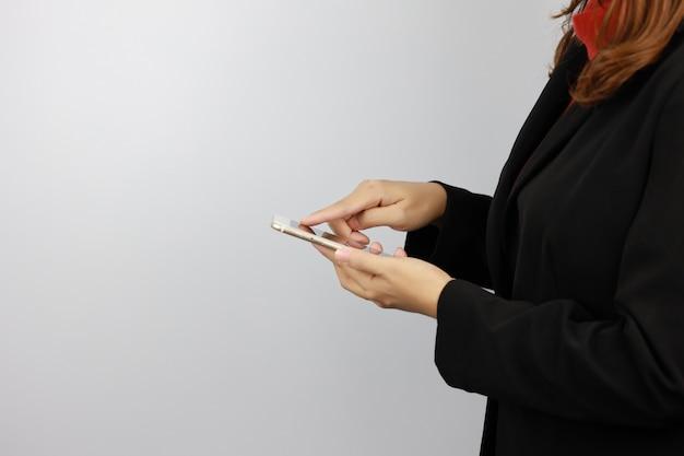 Seitenansicht-geschäftsfrau, die schwarze und rote geschäftsanzuguniform trägt, die handy mit selbstbewusstsein hält und berührt