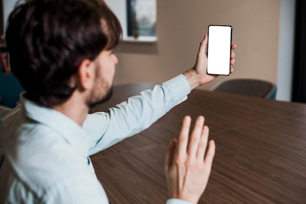 Seitenansicht-geschäftsmann, der auf einem videoanruf spricht