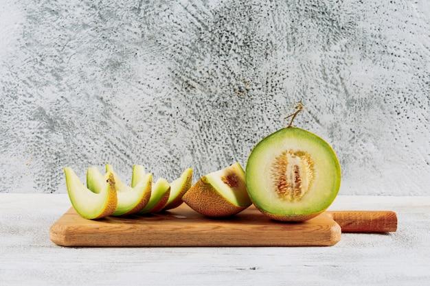 Seitenansicht geschnittene melone mit in zwei hälften geteilter melone auf schneidebrett auf weißem steinhintergrund. horizontaler raum für text
