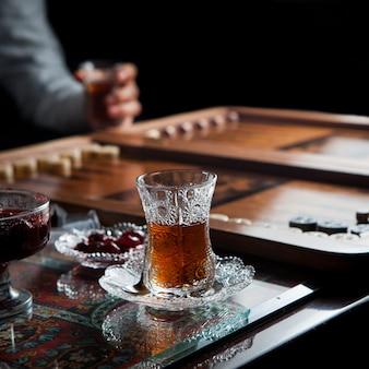 Seitenansicht glas tee mit backgammon und menschlicher hand und marmelade in der fassung auf teppich tisch