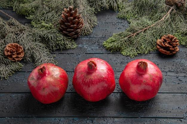 Seitenansicht granatäpfel auf tisch drei reife granatäpfel neben ästen mit zapfen in der mitte des tisches