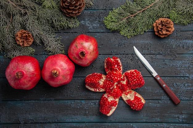 Seitenansicht granatäpfel auf tisch pilled granatapfel neben drei roten granatapfelmesser und fichtenzweigen mit zapfen