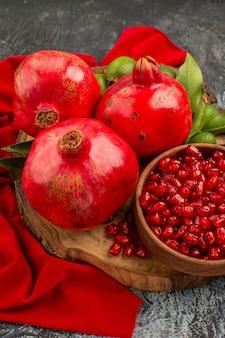 Seitenansicht granatapfelkerne granatapfel drei granatäpfel mit blättern auf dem holzbrett