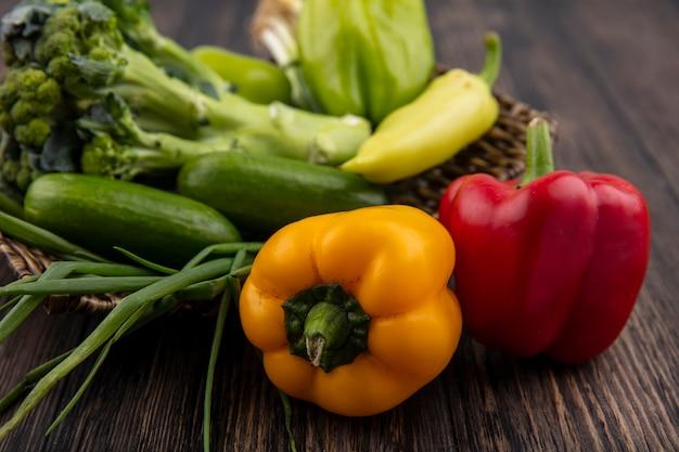 Seitenansicht gurken mit farbigem paprikabrokkoli und frühlingszwiebeln auf hölzernem hintergrund