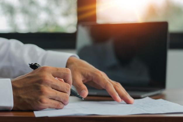 Seitenansicht-handschreibstift auf dokumentcomputerhintergrund, nahaufnahmehandstiftzeichen auf papierkram