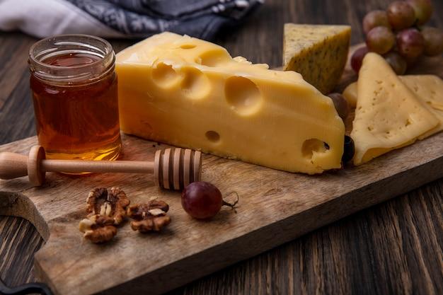 Seitenansicht honig in einem glas käse und walnüssen mit trauben auf einem ständer