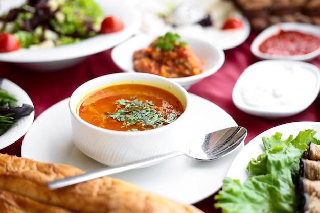 Seitenansicht hühnerbrühe suppe mit brot auf einem servierten tisch