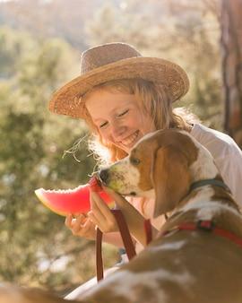 Seitenansicht hund und frau, die eine scheibe wassermelone essen