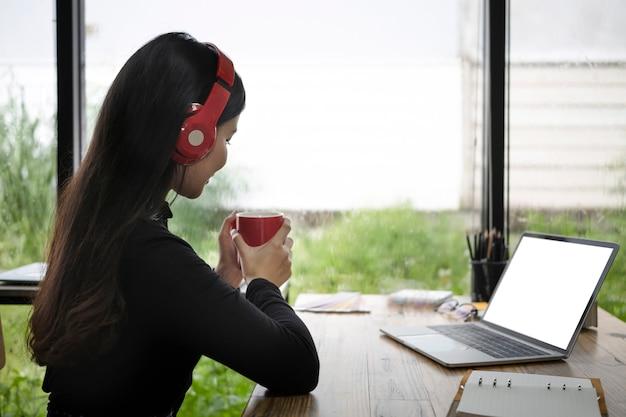 Seitenansicht junge asiatische frau, die musik im kopfhörer hört und heißen kaffee im büro trinkt.