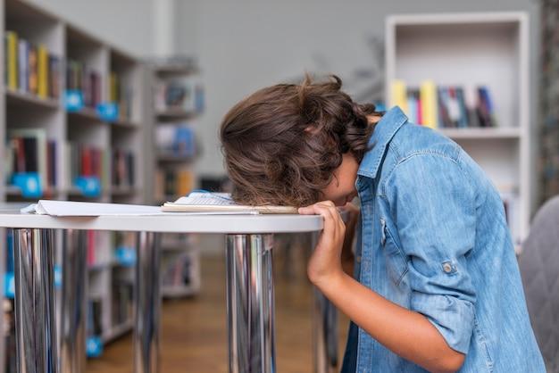 Seitenansicht junge, der auf seinem notizbuch schläft