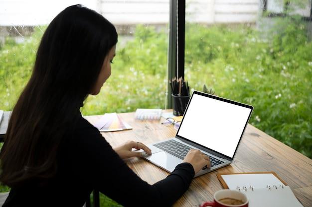 Seitenansicht junge frau, die mit computerlaptop ein haus arbeitet.