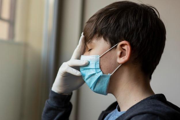 Seitenansicht junge mit medizinischer maske, die sein gesicht berührt